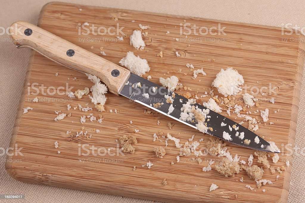 Bread crumbs on cutting board with knife royalty-free stock photo