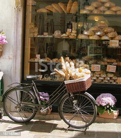 Bread Delivery Bike in Italy with bread in its basket. The background is a bakery window with a variety of bread loaves.