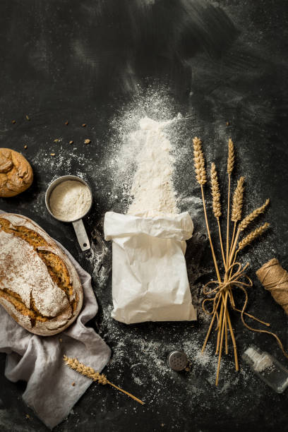 Bread, flour bag, wheat and measuring cup on black Flour sprinkled from the white paper bag, rustic bread, measuring cup and ears of wheat - kitchen. Captured from above (top view, flat lay) on black chalkboard background. Layout with free text space. baking bread stock pictures, royalty-free photos & images