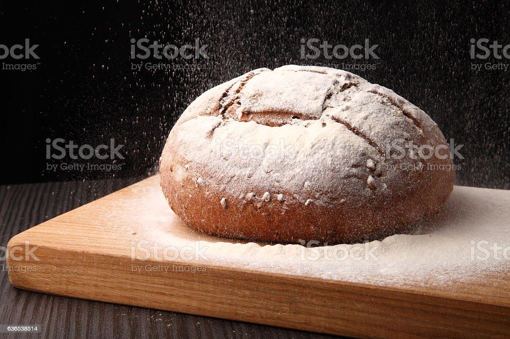 bread, flour sprinkled on an oak board stock photo