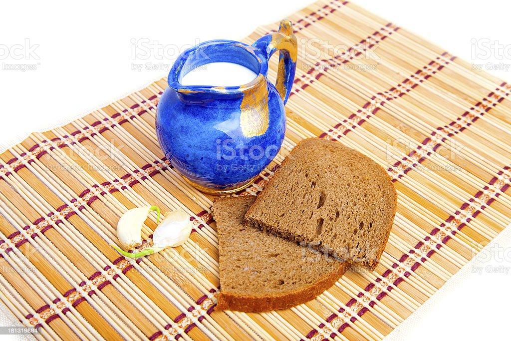 Bread, garlic, and milk on kitchen mat royalty-free stock photo