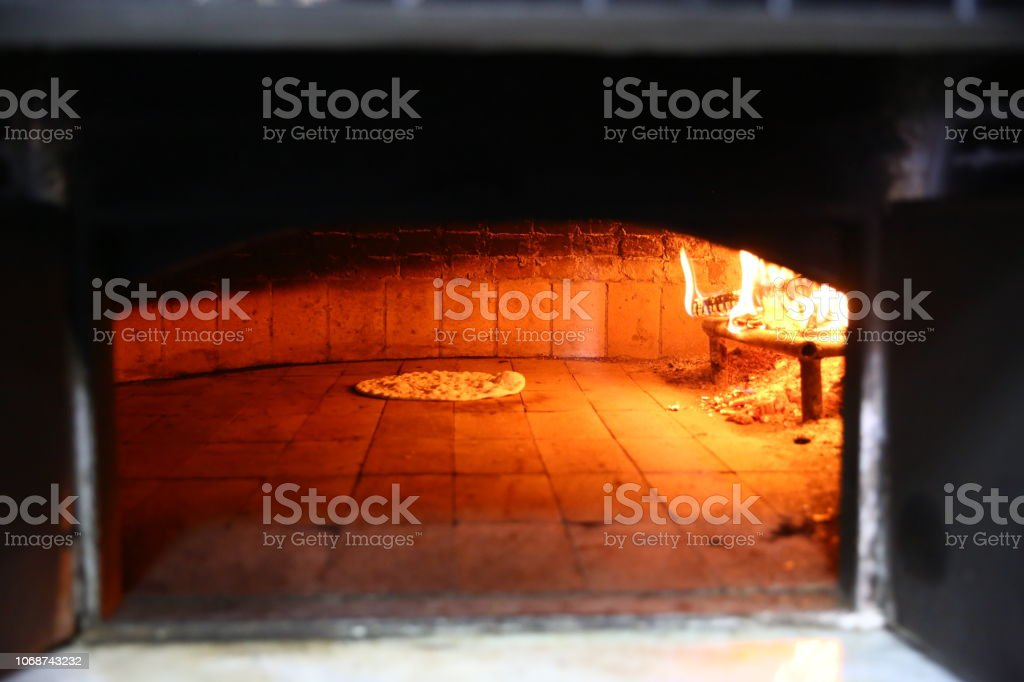 Bread in front of ancient burning wood oven stock photo