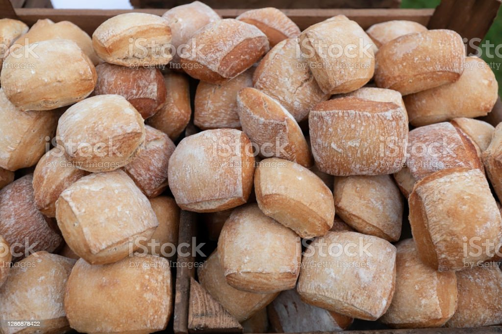 Bread in heaps in a wooden box. Mixed fresh breads. Food, bakery concept. Rectangular buns, in a pile in a wooden crate. Arrangement Stock Photo