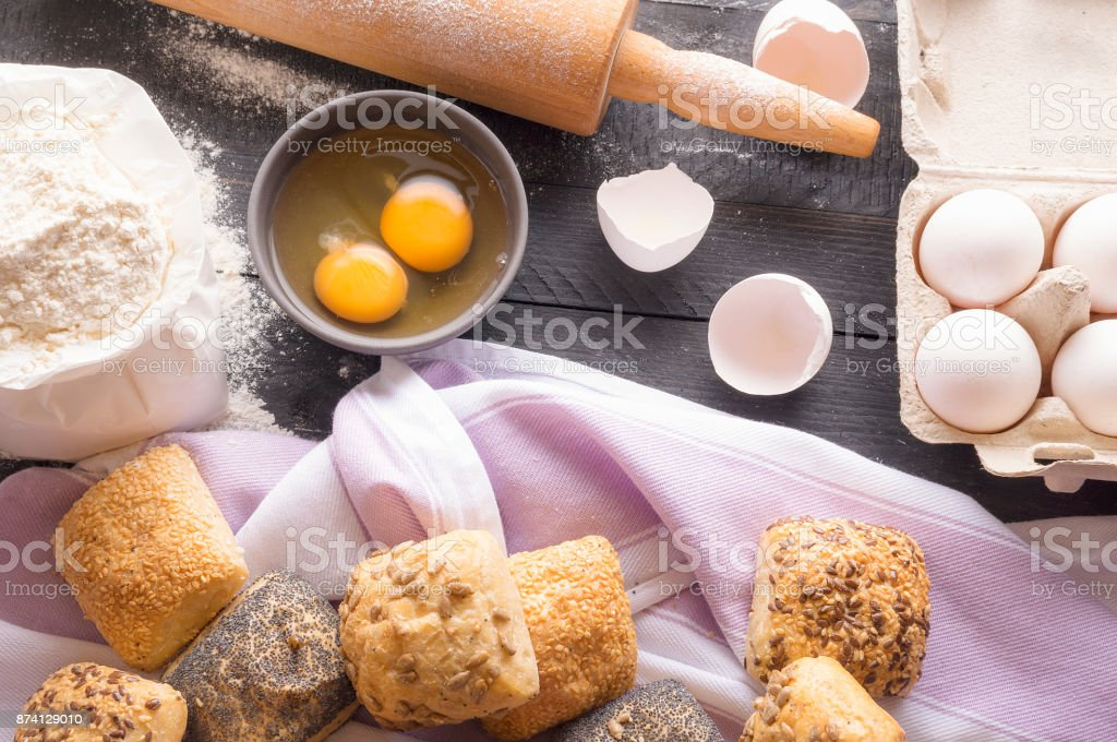 Bread ingredients and homemade buns stock photo
