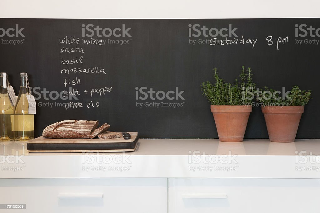 Bread On Chopping Board With Shopping List Blackboard stock photo