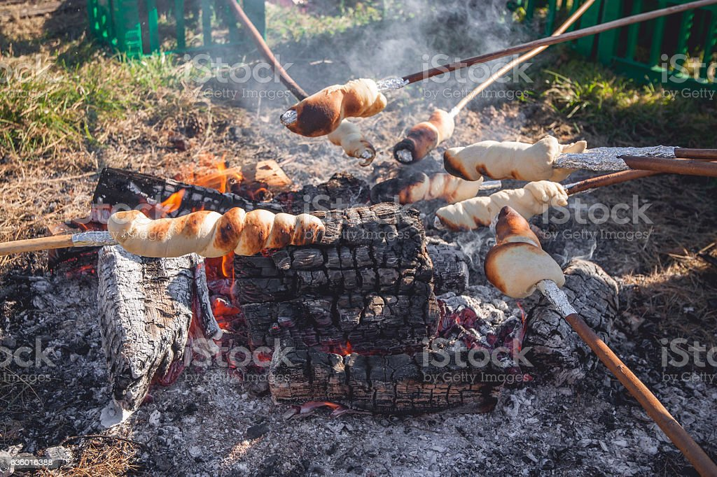Bread on sticks over an outdoor campfire stock photo