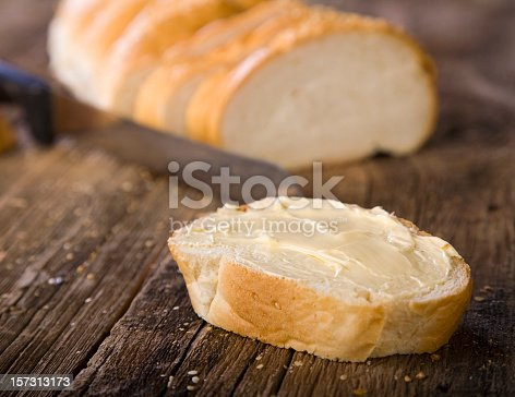 A slice of French bread on a rustic wooden counter.