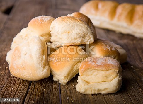 A pile of dinner rolls on a rustic wooden counter.