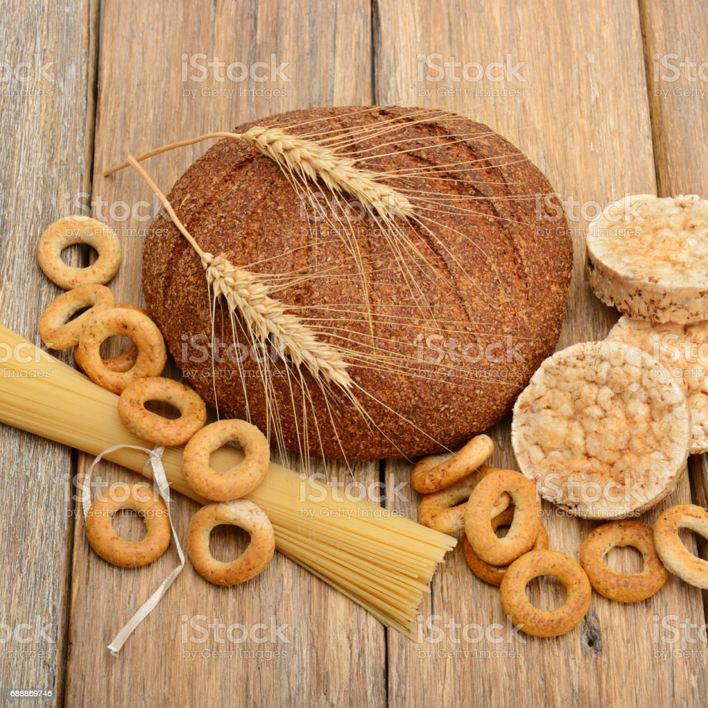 bread, pasta and pastries on a wooden surface stock photo