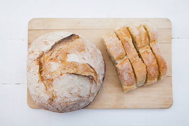 Bread Bread loaf and slices on a cutting board round loaf stock pictures, royalty-free photos & images
