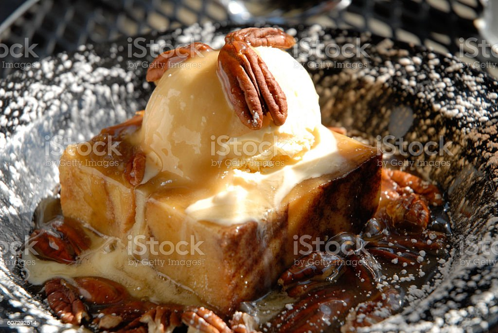 Bread Pudding with Ice Cream Pecans and Powdered Sugar stock photo