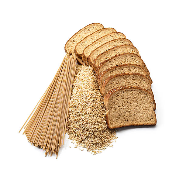 Bread, rice and pasta from whole grains on white backdrop Whole grain bread slices, heap of brown rice and whole grain pasta carefully arranged on white backdrop. These are whole grain healthy eating food products specially indicated for dieting. The brown rice is in the center while the bread slices are on the top and the pasta is on the left whole wheat stock pictures, royalty-free photos & images
