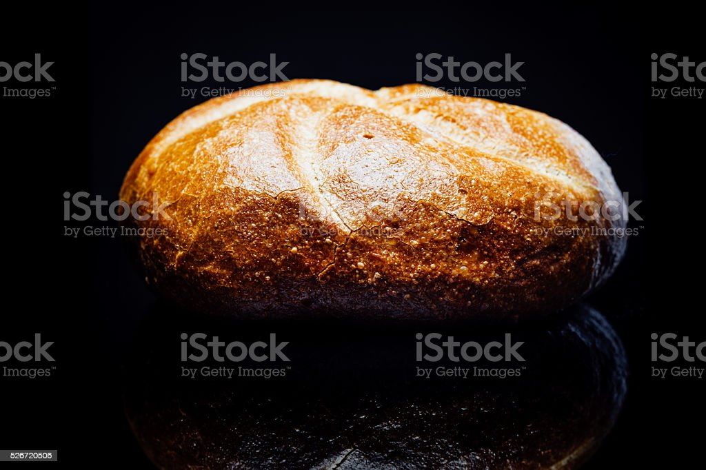 Bread roll, on black background, reflection stock photo
