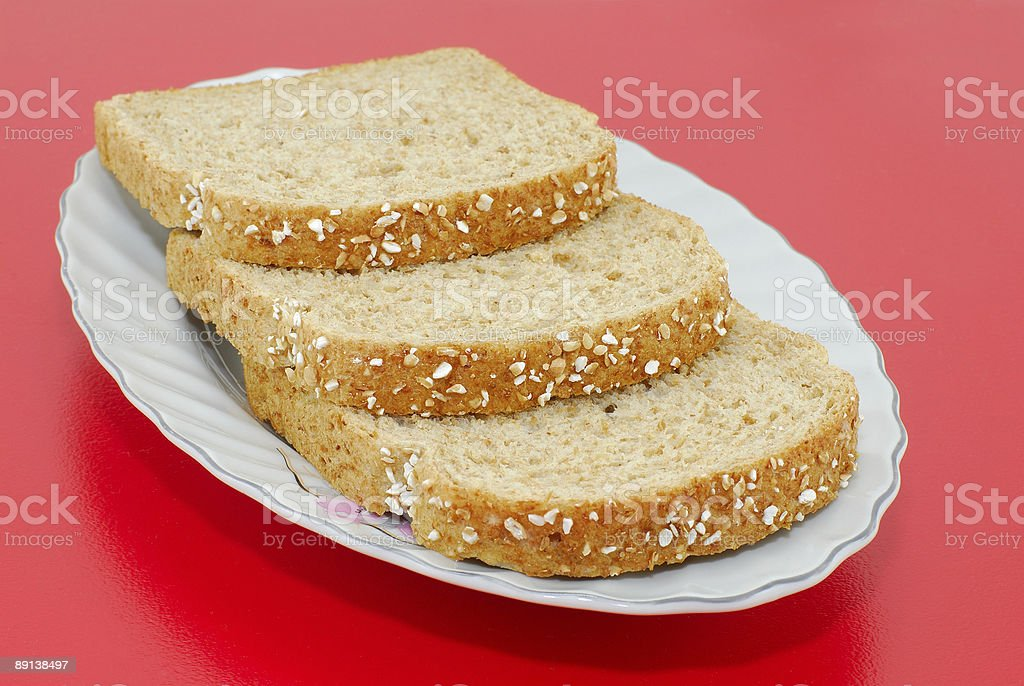 Bread slices on the red background royalty-free stock photo