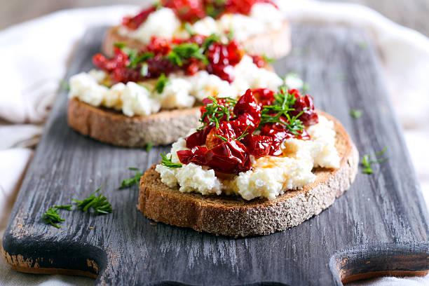 Fette di pane con ricotta e, pomodori essiccati - foto stock