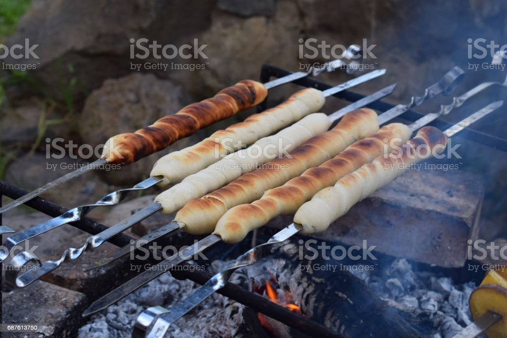 bread sticks of dough cooked on a fire. Italian breadsticks from wholemeal flour with herbs stock photo