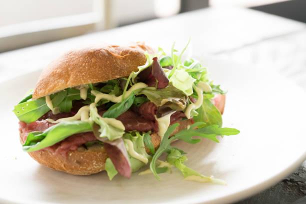 brot mit rindercarpaccio, salat und sauce auf weißen teller - carpaccio salat stock-fotos und bilder