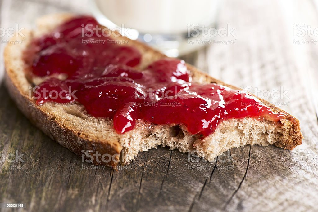 Bread with strawberry jam bited stock photo