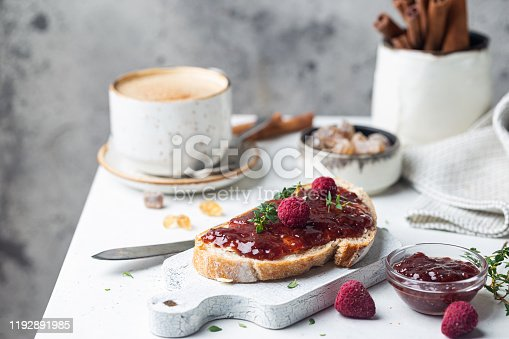 Toasted bread with sweet raspberry jam for breakfast on light background