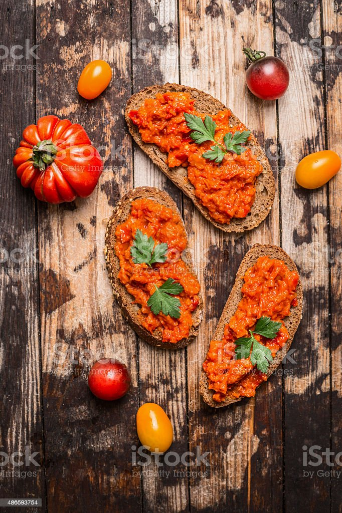 Bread with tomato spread on rustic wooden background, top view. stock photo
