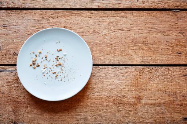 breadcrumbs on empty plate - briciola foto e immagini stock