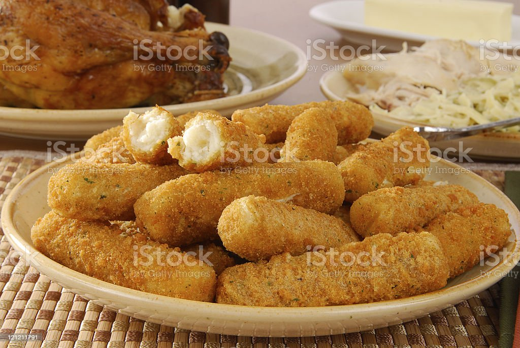 Breaded cheese sticks on a plate with table of food stock photo