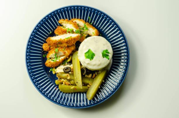 Filé de peito de frango empanado servido com purê de batatas e gherkin com azeitonas - foto de acervo