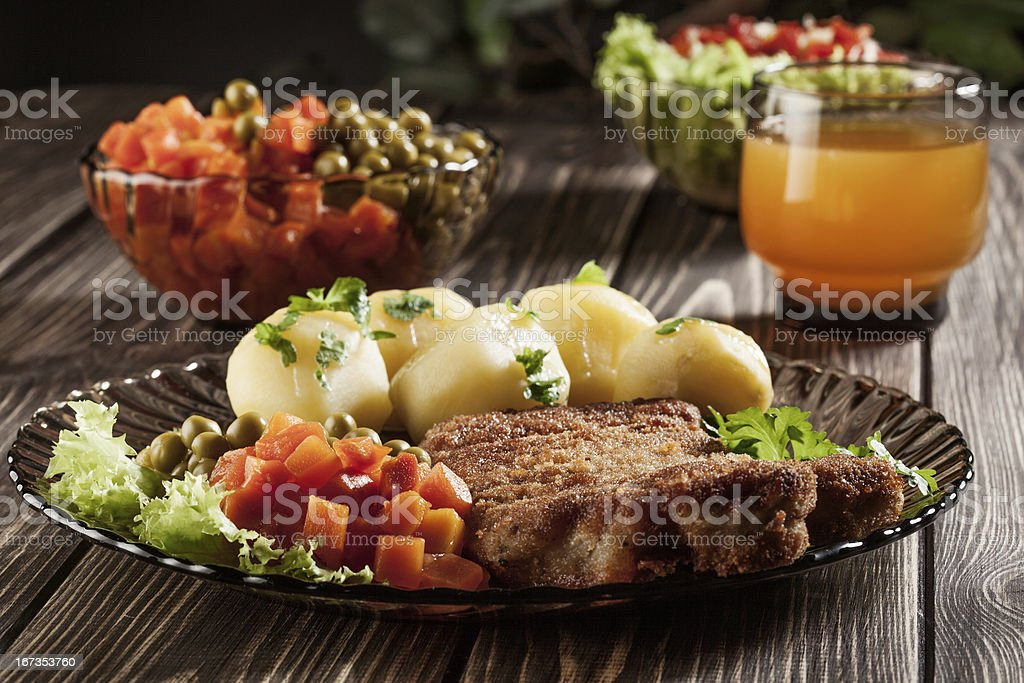 Breaded chop and potatoes. stock photo