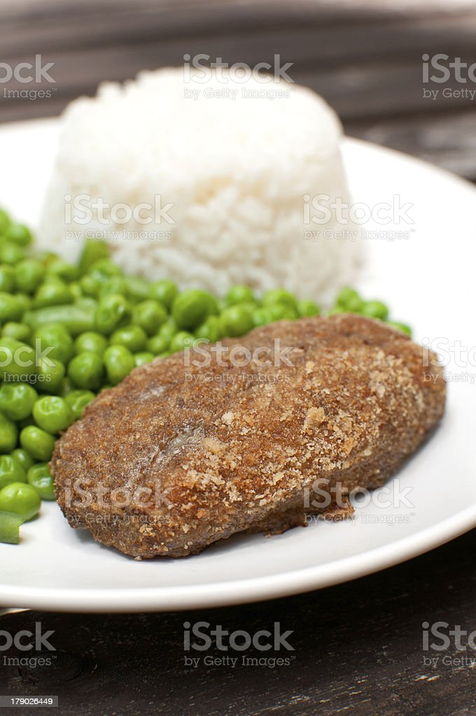 Breaded cutlet with rice and green salad royalty-free stock photo