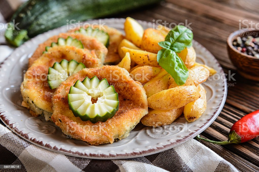 Breaded fried zucchini with American potatoes and cucumber stock photo