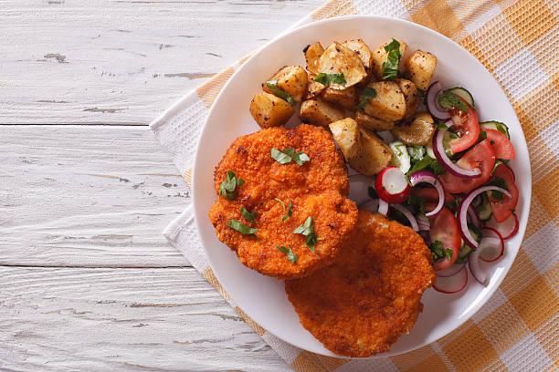breaded german weiner schnitzel with potatoes. horizontal top view - kürbisschnitzel stock-fotos und bilder