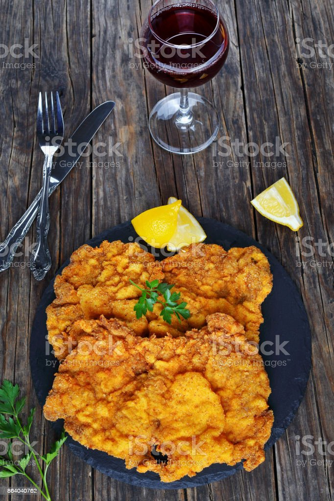 breaded veal cutlets on black stone plate stock photo