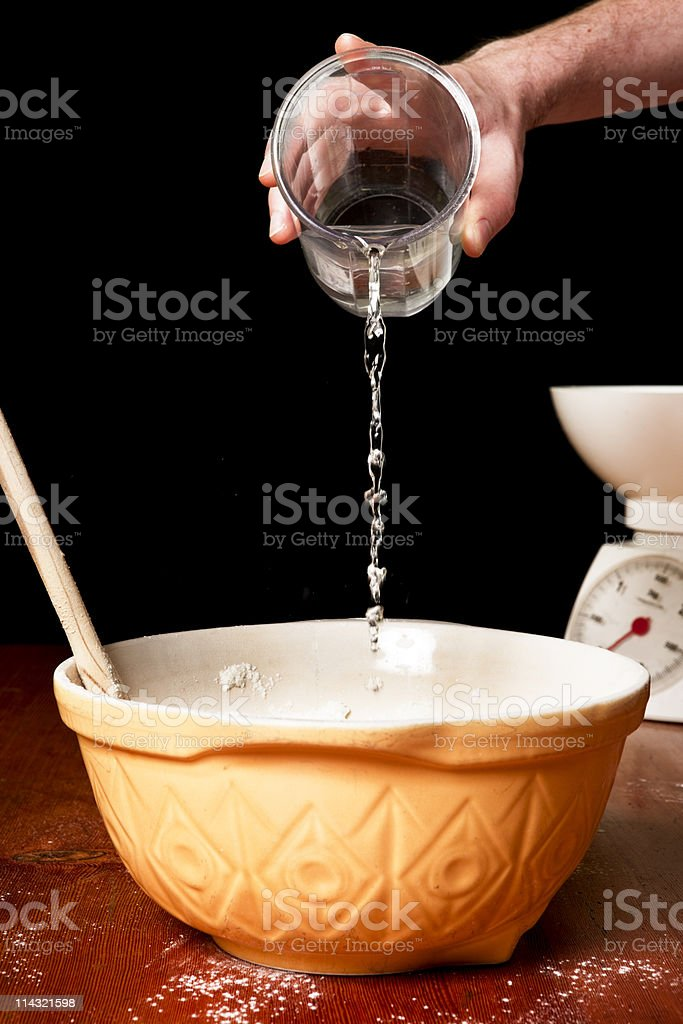 Breadmaking: Adding water to dough stock photo