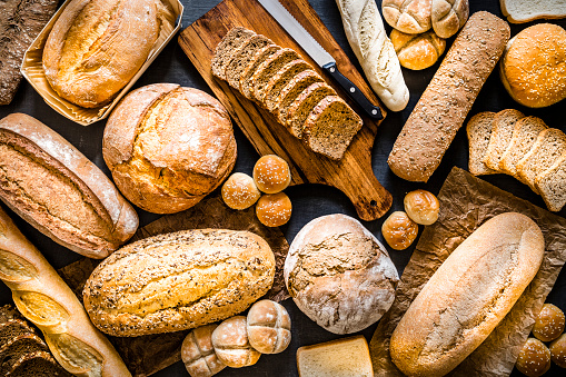 Top view of various kinds of breads like brunch bread, rolls, wheat bread, rye bread, sliced bread, wholemeal toast, spelt bread and kamut bread. Breads are scattered making a background. Low key DSLR photo taken with Canon EOS 6D Mark II and Canon EF 24-105 mm f/4L
