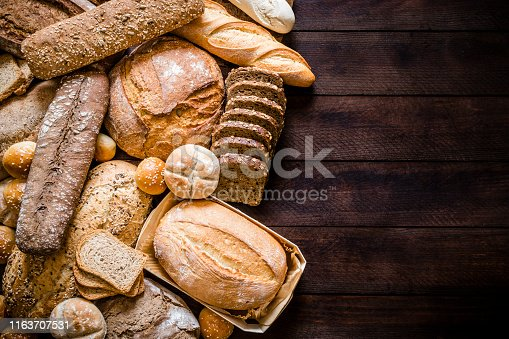 Top view of breads assortment like brunch bread, rolls, wheat bread, rye bread, sliced bread, wholemeal toast, spelt bread and kamut bread on dark brown rustic wooden table. Breads are at the left side of the image leaving a useful copy space at the right side on the table. Low key DSLR photo taken with Canon EOS 6D Mark II and Canon EF 24-105 mm f/4L