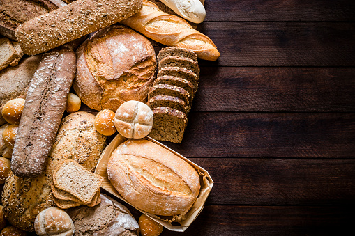 Breads assortment with copy space on rustic wooden table
