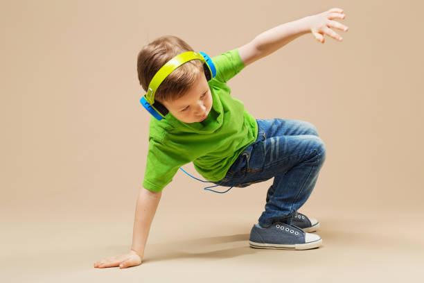 break dance kids. little break dancer showing his skills in dance studio. Hip hop dancer boy in headphones with smartphone against studio background stock photo