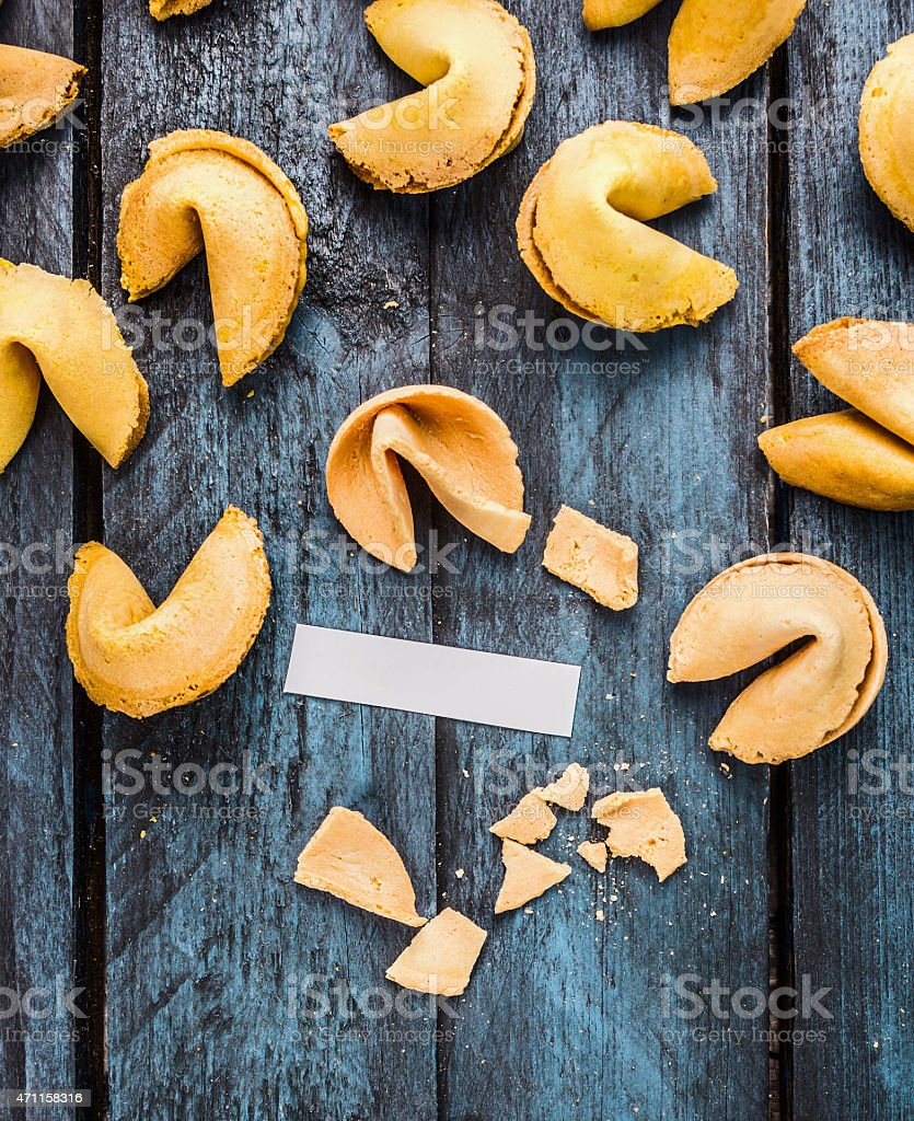 break fortune cookie with  blank paper tag on  wooden background stock photo