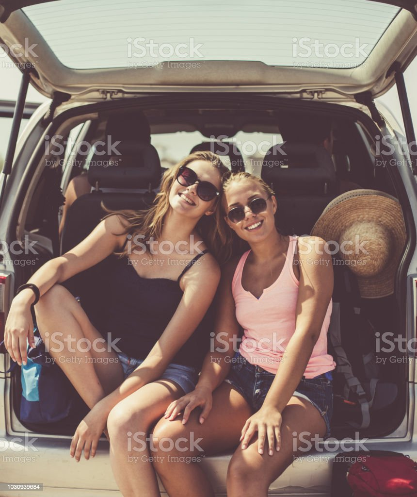 Two female friends are sitting on car trunk and taking a break from a...