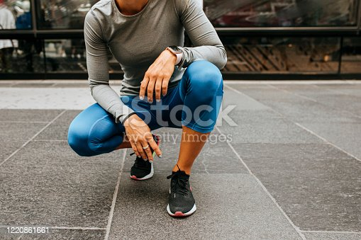 Break from the Workout: Runner in Blue Tights Squating on the Street