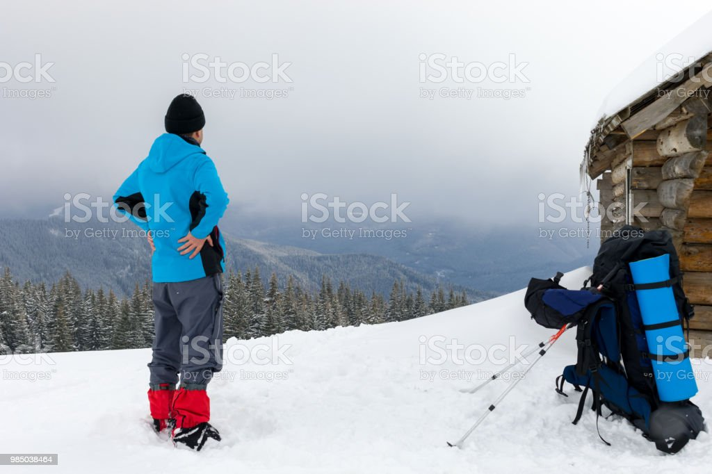 A hiker has a rest on a top of the snowy Carpathian mountains near...