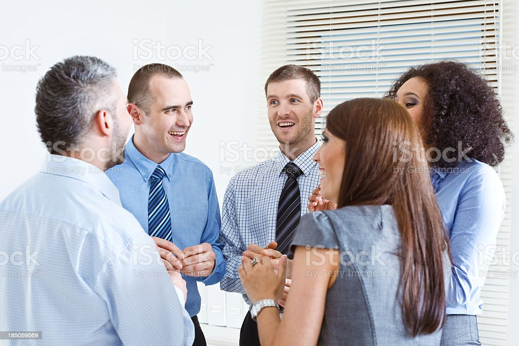 Break in an office Five smiling business people standing in an office and telling funny stories. 25-29 Years Stock Photo
