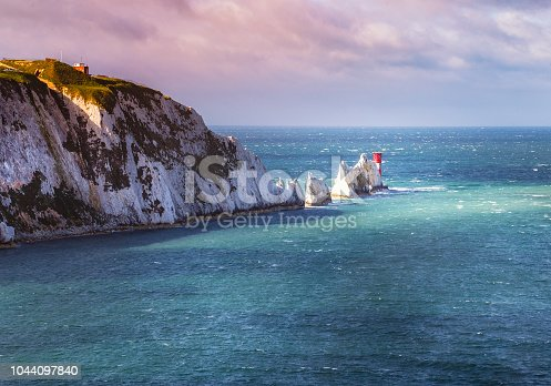 A break in the clouds illuminates the iconic chalk stone pinnacles of The Needles and the 19th century lighthouse on the coastline Isle of Wight an island off the south coast of England