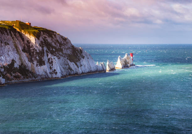 a break in the clouds illuminates the iconic chalk stone pinnacles of the needles and the 19th century lighthouse on the coastline isle of wight an island off the south coast of england - english channel stock pictures, royalty-free photos & images