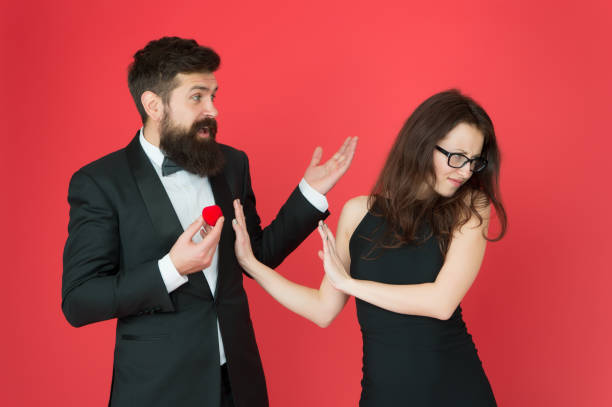 Break off wedding engagement. Bearded man give wedding ring to sensual woman. Couple in love in formal wear. Celebrate wedding anniversary. Shell be ok for wedding day stock photo