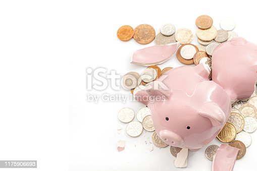 Break the bank, economic downturn and bankruptcy concept theme with a broken piggy bank and scattered coins isolated on white background with copy space