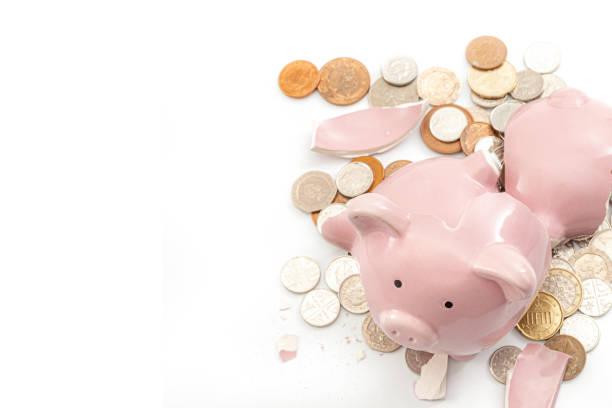 Romper el banco, la recesión económica y el tema del concepto de bancarrota con una alcancía rota y monedas dispersas aisladas sobre fondo blanco con espacio de copia - foto de stock