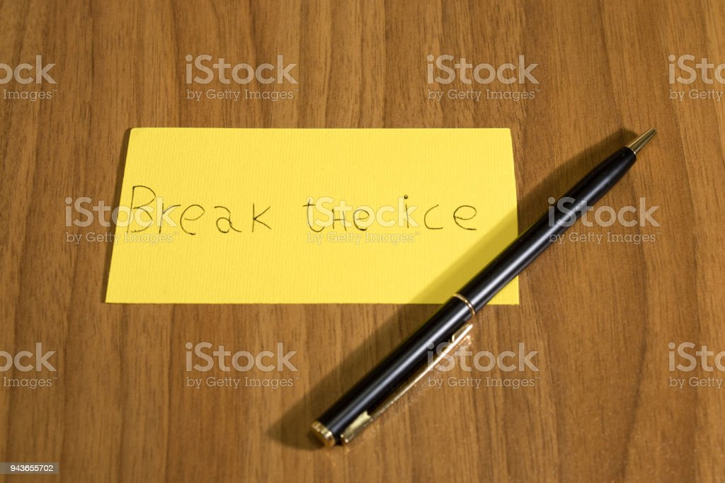 Break the ice handwrite on a yellow paper with a pen on a table composition stock photo