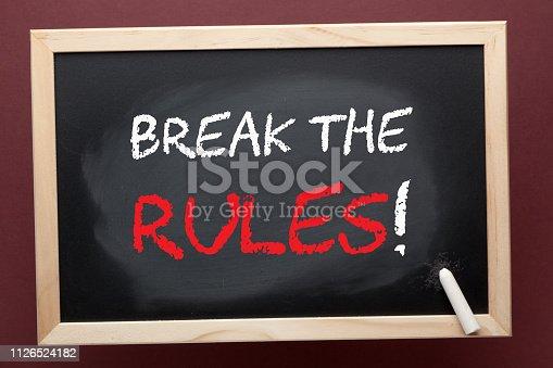 Break the rules written on blackboard by white chalk. Business concept.
