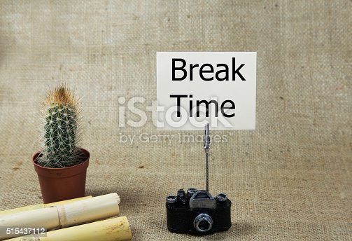 break time written orange note paper on a holder and on burlap background. crayons retro design